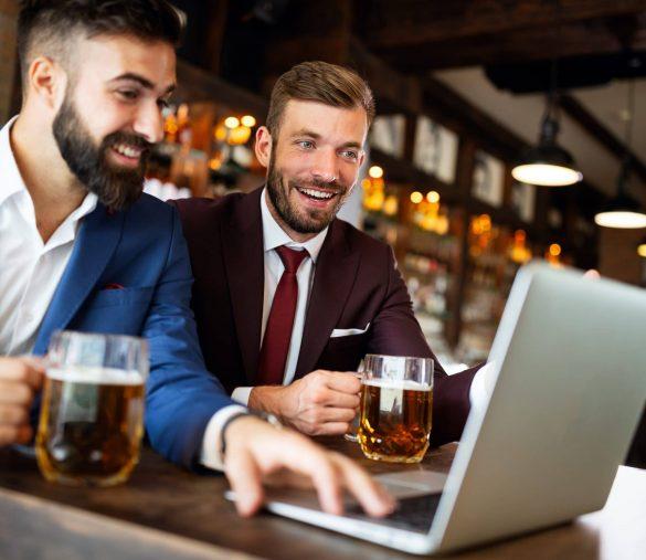 Business people drink beer after work. Businessmen enjoy a beer at a pub