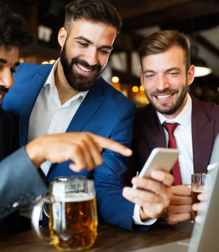 Group of happy business men drinking beer at the pub and having fun