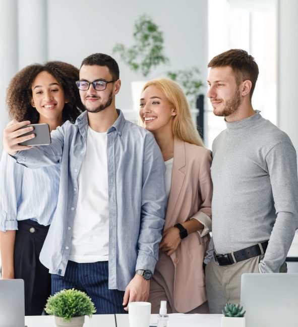 Selfie at work with colleagues. Multiracial workers looking at smartphone camera, guy makes photo in interior of modern office or video about company and corporate culture for clients, copy space