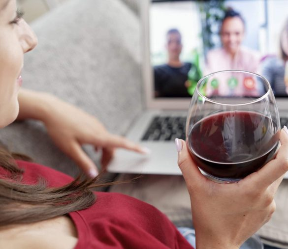 Woman drinking wine during video conference with friends